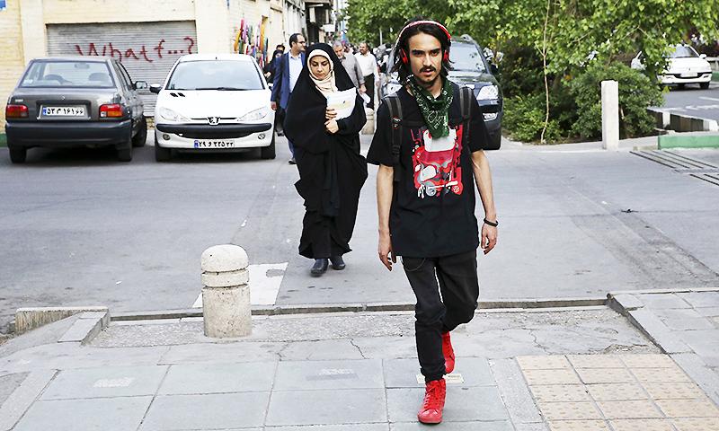 Iranian women make their way along a sidewalk in downtown Tehran, Iran. ─ AP