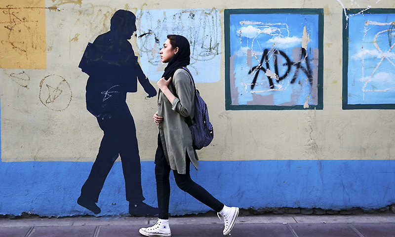 An Iranian woman walks past a mural in a sidewalk in downtown Tehran. ─ AP
