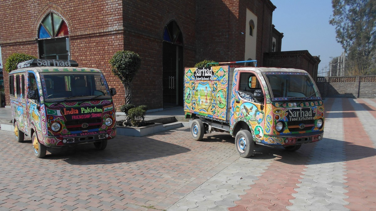 Displayed on the main entrance of Sarhad are a pair of vans, embellished with Pakistani truck art