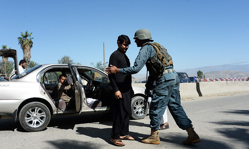An Afghan policeman (R) searches a passenger in the city of Jalalabad, close to the border with Pakistan, on April 29, 2016, after reports that an aid worker from Perth has been kidnapped by armed men in Jalalabad. — AFP