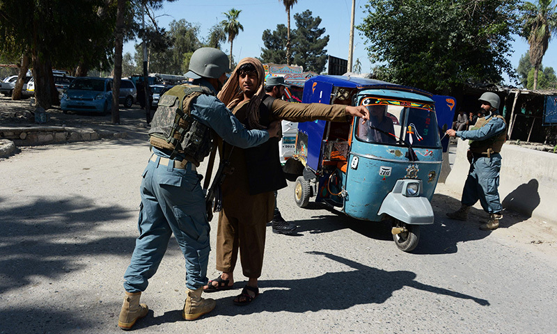 An Afghan policeman searches a passenger in the city of Jalalabad, close to the border with Pakistan, on April 29, 2016, after reports that an aid worker from Perth has been kidnapped by armed men in Jalalabad. -AFP