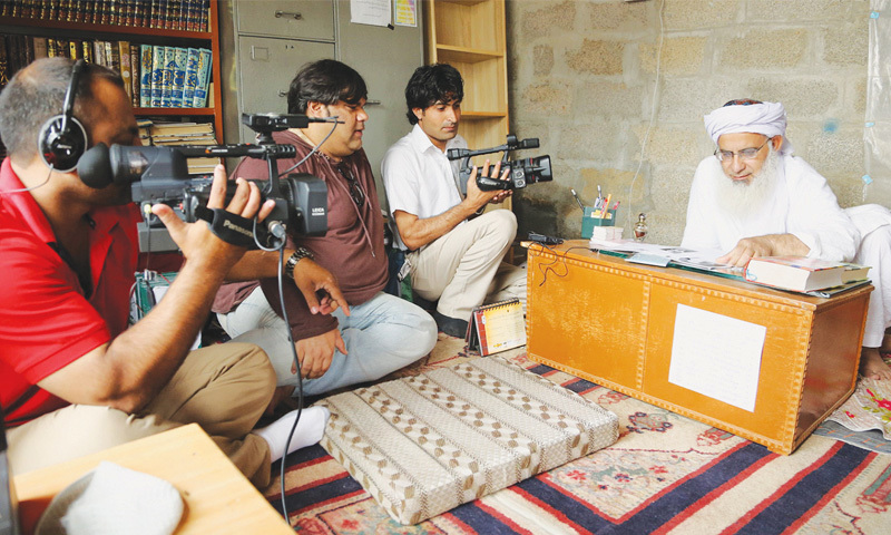 Maulana Abdul Aziz reads from a book during the filming of the documentary.—Image courtesy Manjusha Films and Changeworx1