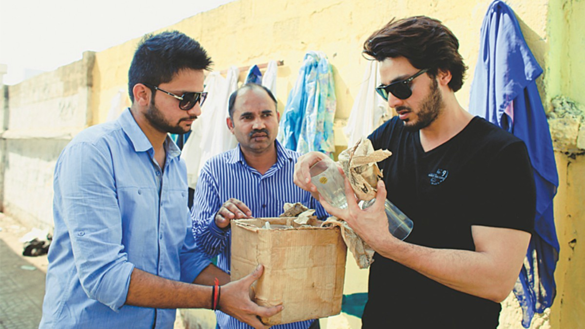 Ahsan Khan with volunteers at the Wall of Kindness on M.A. Jinnah Road
