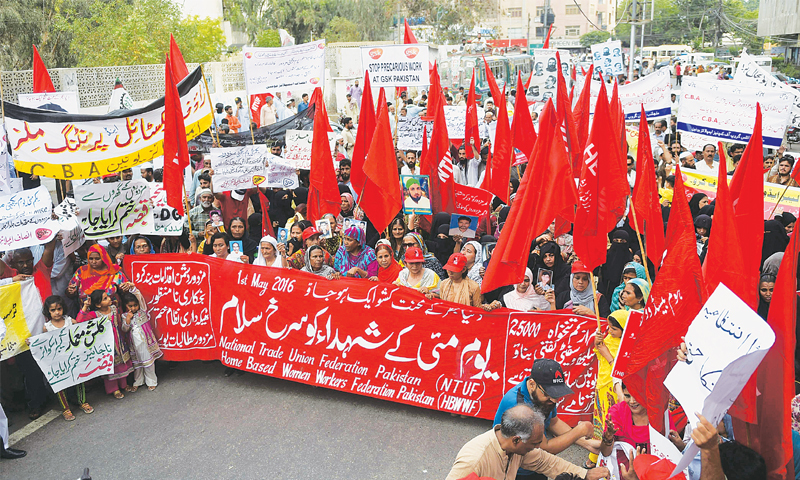 Labour rights activists shout slogans and wave placards inscribed with slogans in favour of workers during a rally on Sunday.—AFP