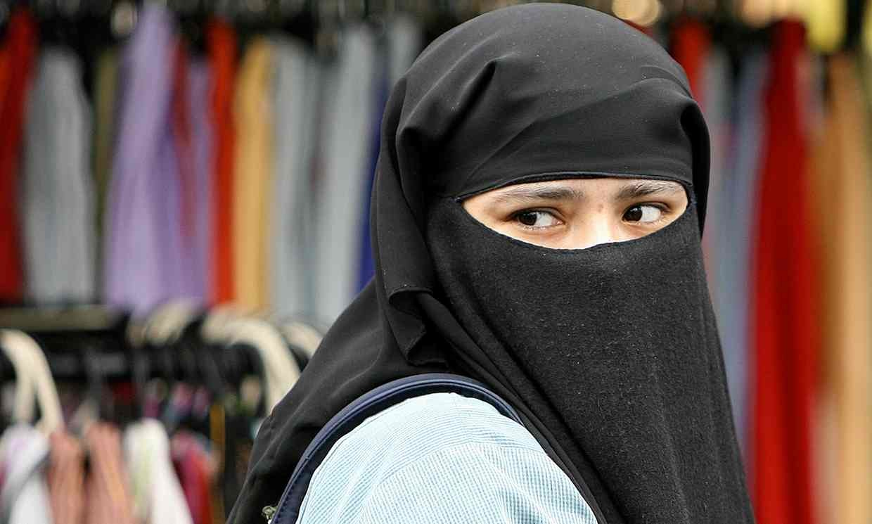 A veiled woman at Whitechapel market in east London | AFP