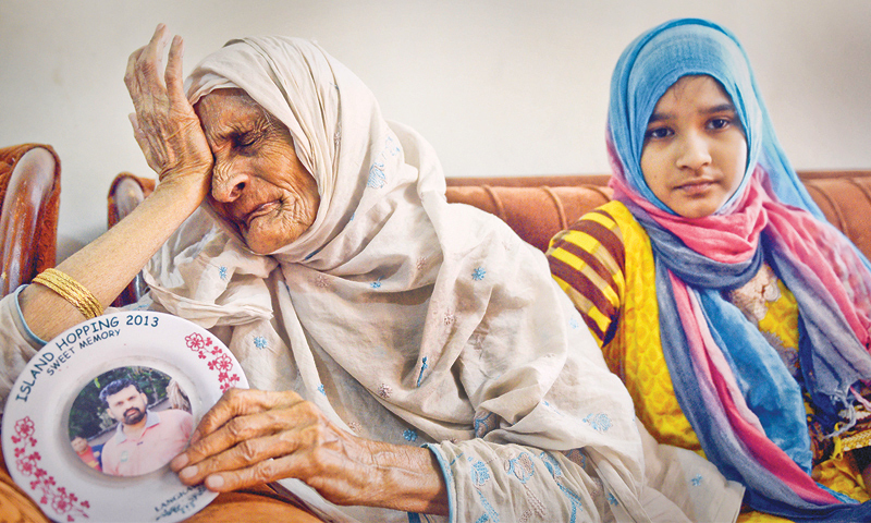 Aftab Ahmed's mother, Saleema Bibi, with his eldest daughter, Tehreem Aftab, 13, mourn his loss at his mother-in-law's home on Wednesday.— Fahim Siddiqi/White Star