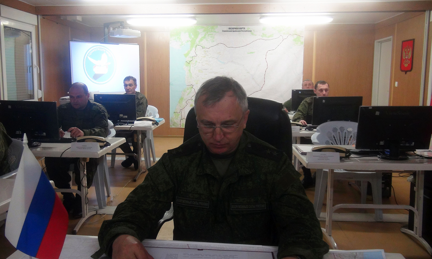 Lieutenant General Sergey Kirilenko working behind his desk in Russia's ceasefire monitoring centre at the Hmeimim airbase in the northern Syrian province of Latakia. -AFP
