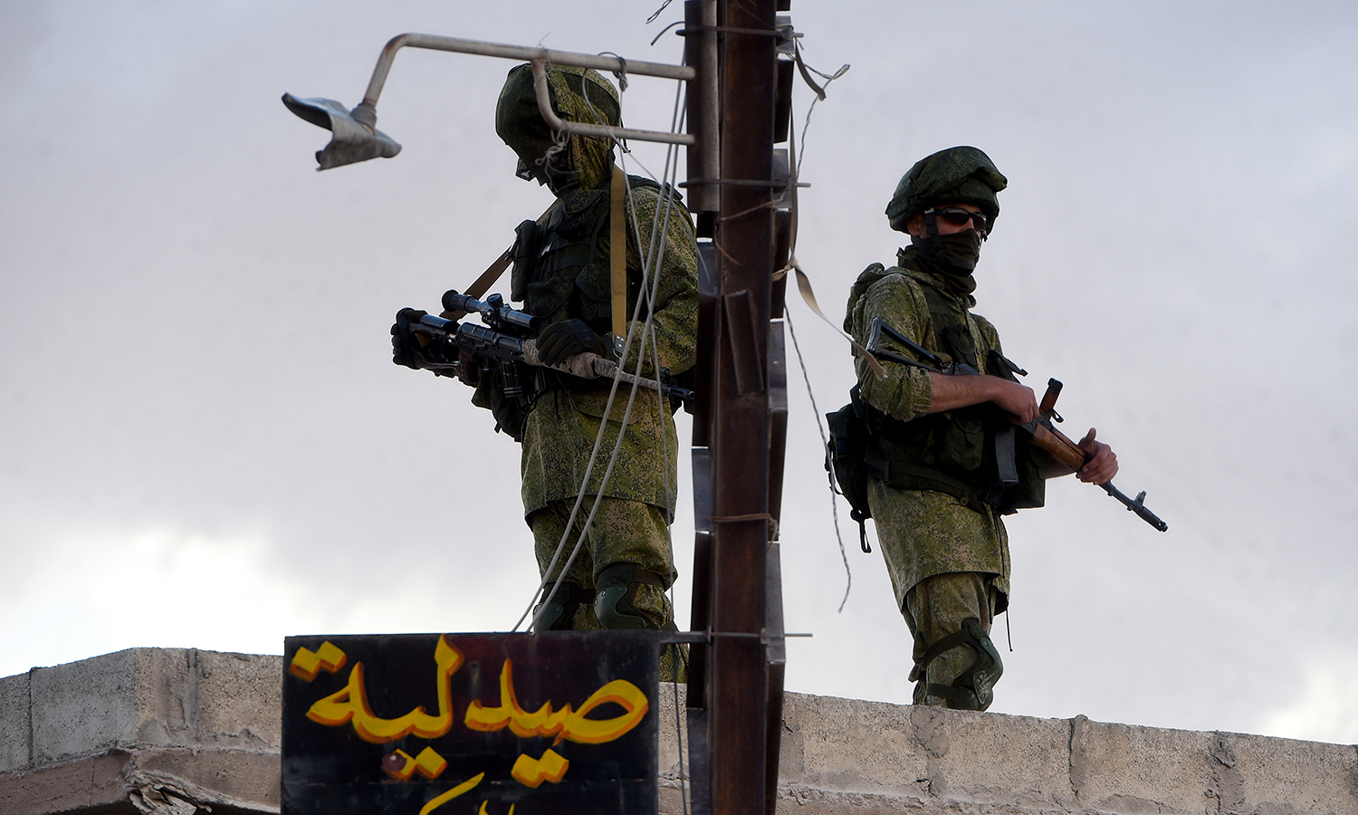 Russian soldiers patrol as a Russian military convoy arrives in a small Syrian village near the city of Hama. -AFP