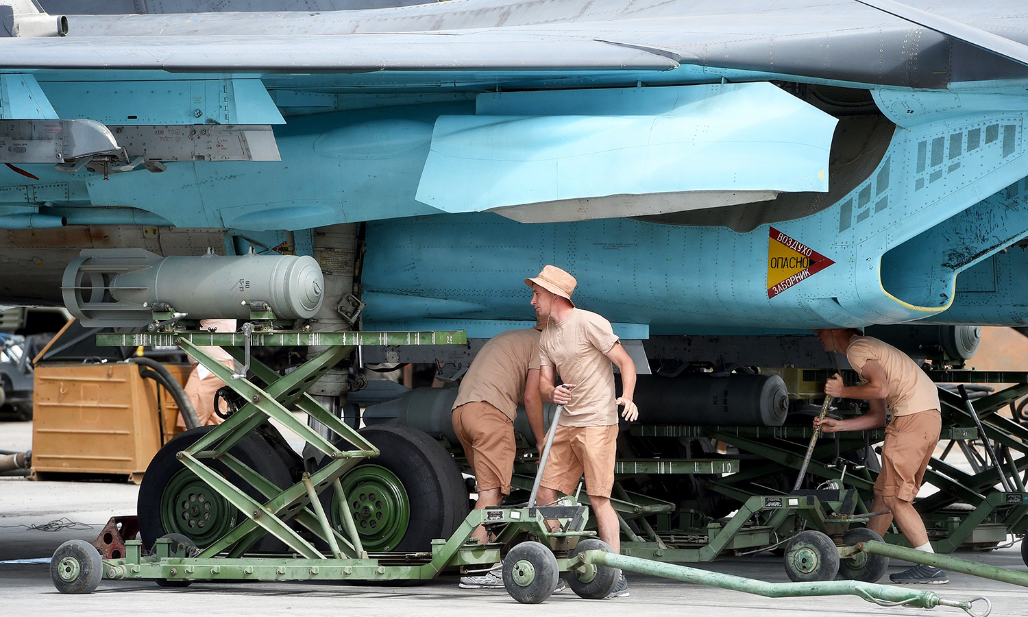 Russian servicemen attach a bomb on an SU-34 fighter jet before a mission from the Russian Hmeimim military base in Latakia. -AFP