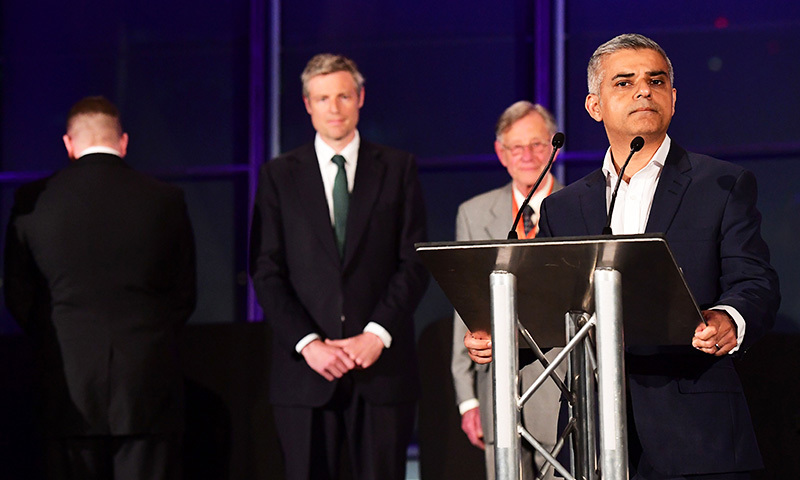 London's new Mayor Sadiq Khan (R) addresses the media as Paul Golding (Far L) the candidate for Britain First, turns his back during the address at City Hall in central London on May 7, 2016. —AFP
