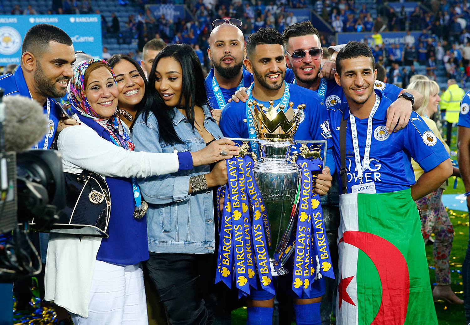 Leicester City's Riyad Mahrez holds the trophy as he celebrates winning the premier league with his family. — Reuters