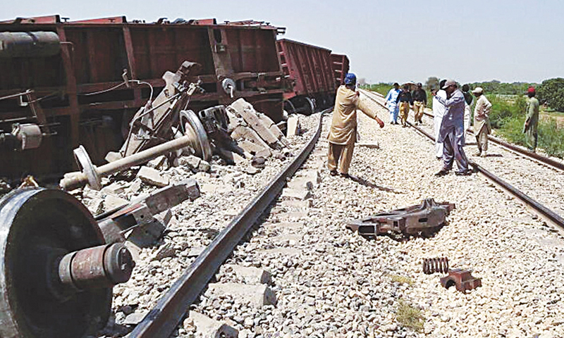 HYDERABAD: Policemen stand near the freight train which derailed after a bomb blast on railway track near Tandojam.—Online