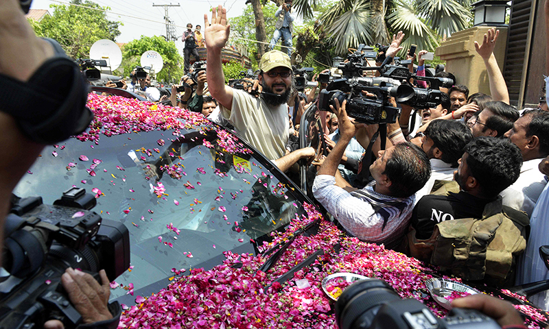 Ali Haider Gilani, waves as he arrives home in Lahore on May 11, 2016. —AFP