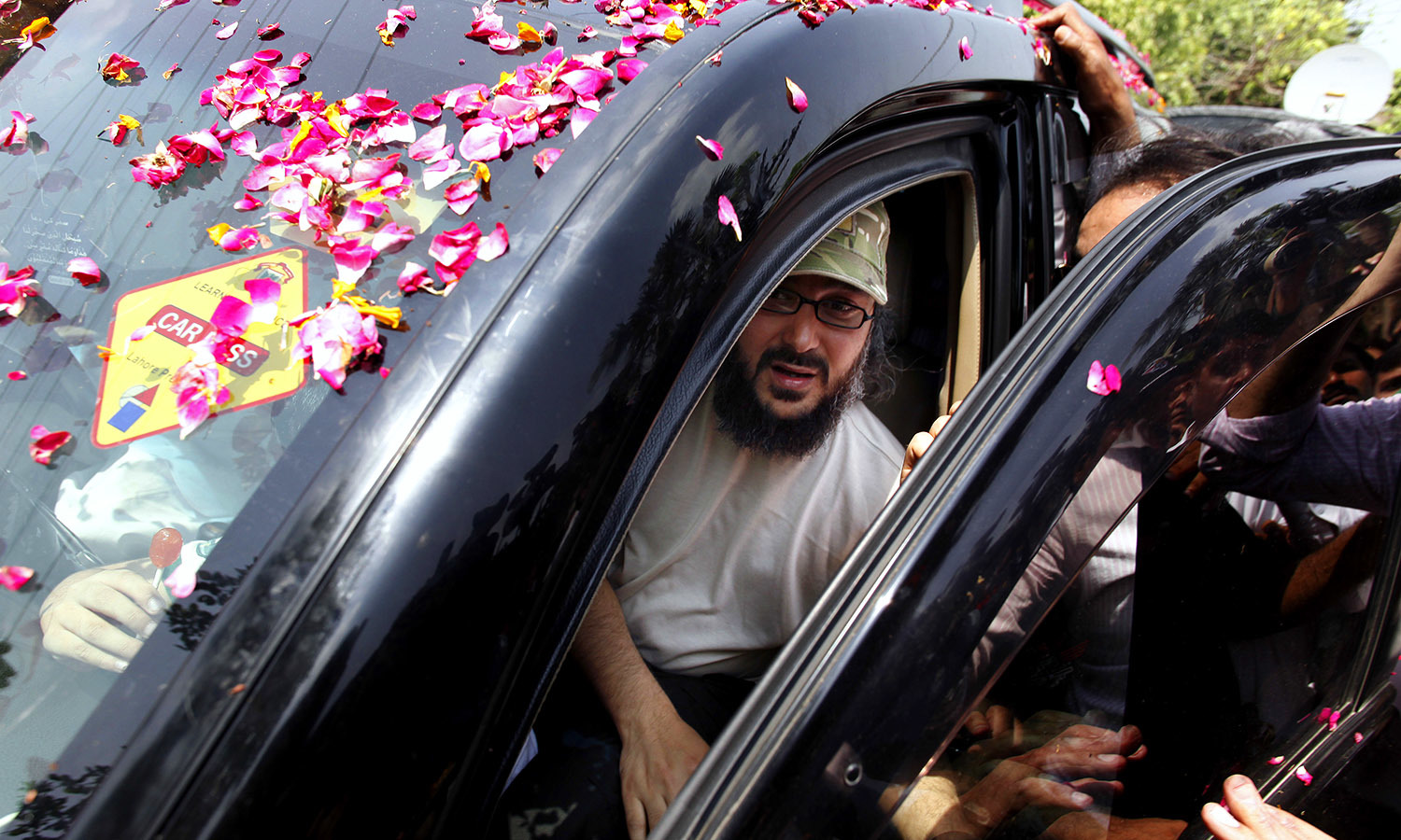 Ali Haidar Gilani disembarks from a vehicle upon arrival at his residence in Lahore ─ AP