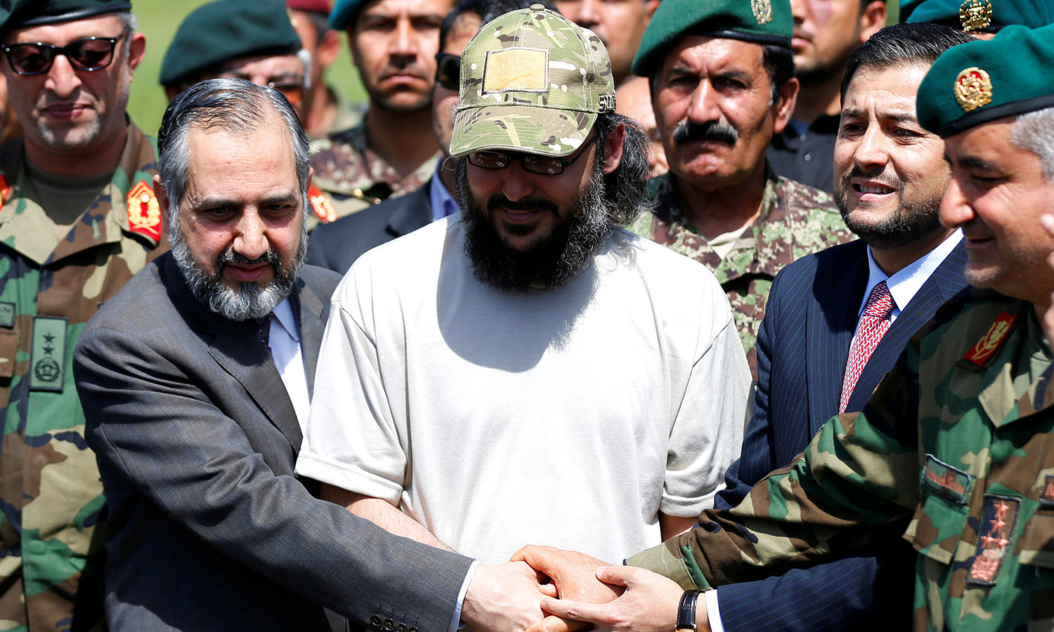 Ali Haider Gilani shakes hands with Afghans and Pakistan's Ambassador to Afghanistan Syed Abrar Hussain (L). -Reuters