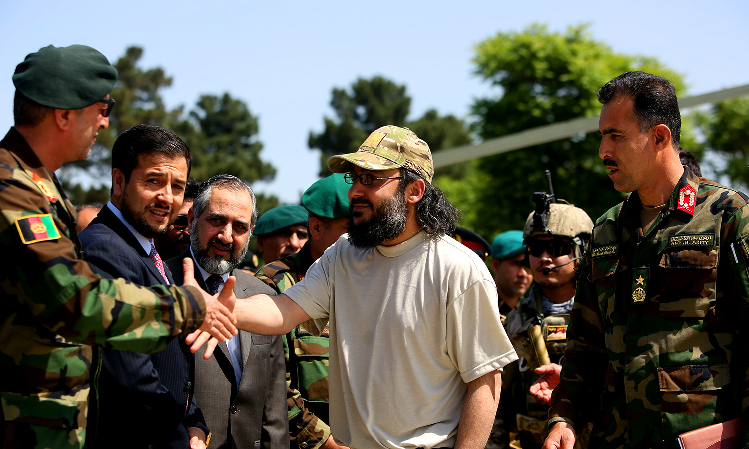 Ali Haidar Gilani, shakes hand with Afghan officials as he arrives at the Afghan Ministry of Defense. -AP
