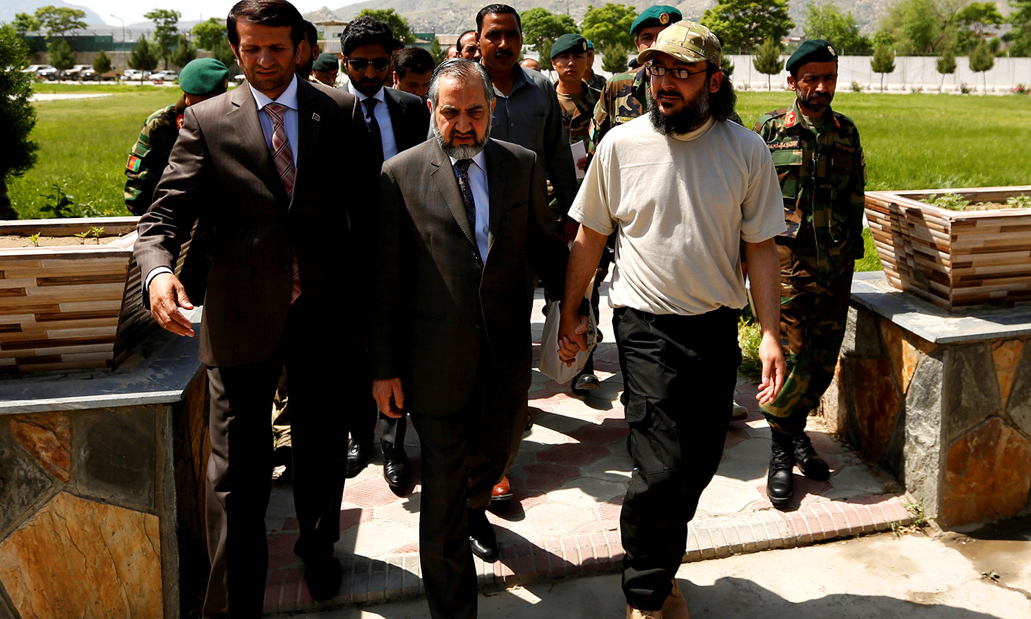 Ali Haider Gilani (L) walks with Pakistan's Ambassador to Afghanistan Syed Abrar Hussain (C) at the Defence ministry. -Reuters