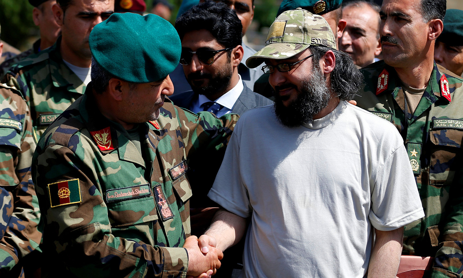 Ali Haider Gilani (R) shakes hands with Afghan Joint Chief of Staff Gen. Qadamshah Shahim at the Defence Ministry. -Reuters
