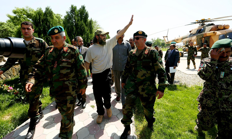 Ali Haidar Gilani waves as he arrives at the Ministry of Defense. -AP