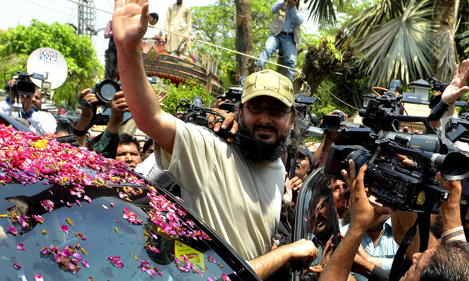 Ali Haider Gilani, waves as he arrives home in Lahore. -AFP