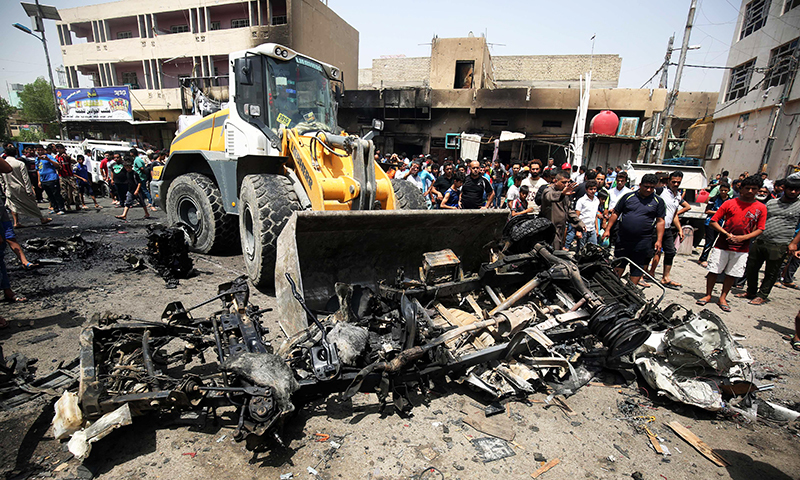 A bulldozer clears the wreckage following a car bomb attack in Sadr City. -AFP