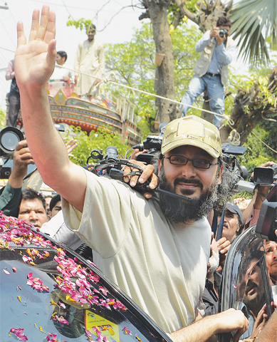 LAHORE: Ali Haider Gilani, son of former prime minister Yousuf Raza Gilani, waves as he arrives here on Wednesday in a shower of rose petals.—AFP