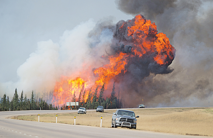 A WILDFIRE burns behind abandoned vehicles on Canada's Alberta Highway 63 near Fort McMurray, Alberta, on May 7.—Bloomberg