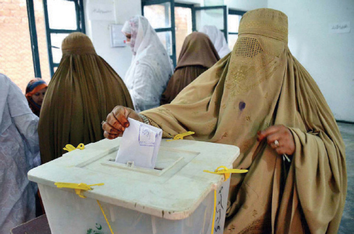 A woman casts vote during by-election in Khazana area of Peshawar on Thursday. — APP