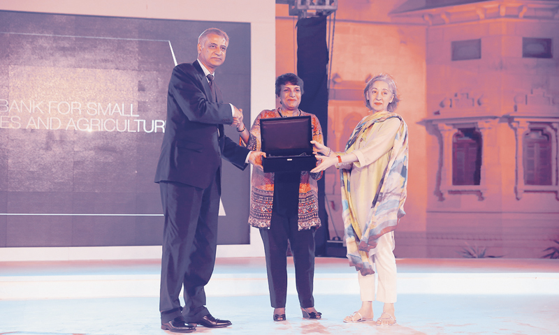 KARACHI: Sima Kamil (centre), HBL's Head of Branch Banking, receives an award from State Bank of Pakistan Governor Ashraf Wathra and Mrs Amber Saigol, chairperson of the Dawn Media Group.
