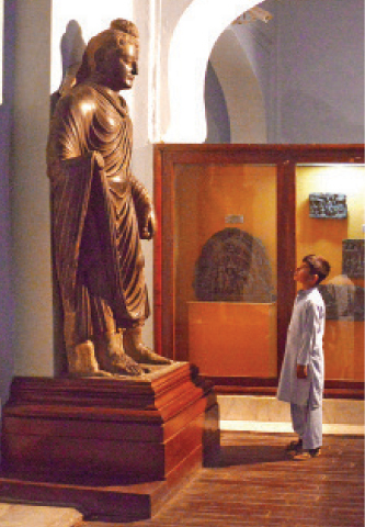 A young visitor takes interest in a Buddha statue at Peshawar Museum on Wednesday. — Photo by Shahbaz Butt