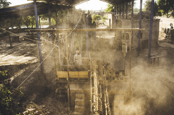 A labourer mixes sand to make mud bricks at a factory on the outskirts of Hyderabad.