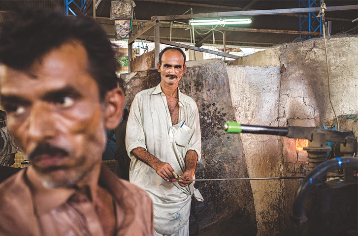 Glass-making is as much an art as it a science; here, a worker at a glass factory melts the glass to pour into pre-made moulds. He makes cosmetic bottles at the factory.