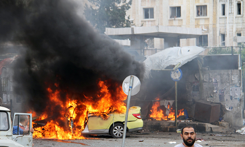 Flames billowing at the scene of multiple bombings in the city of Tartus northwest of Damascus. ─ AFP