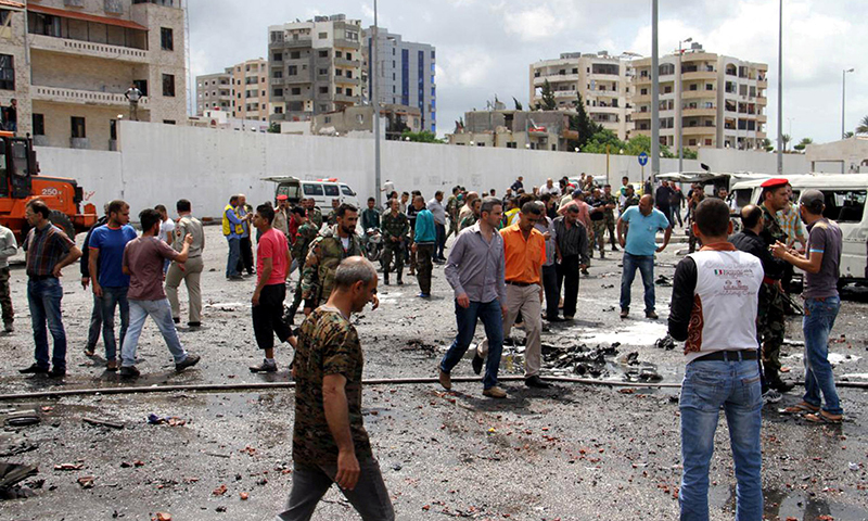 Syrian army soldiers and civilians inspect the damage after explosions hit the Syrian city of Tartous. ─ Reuters
