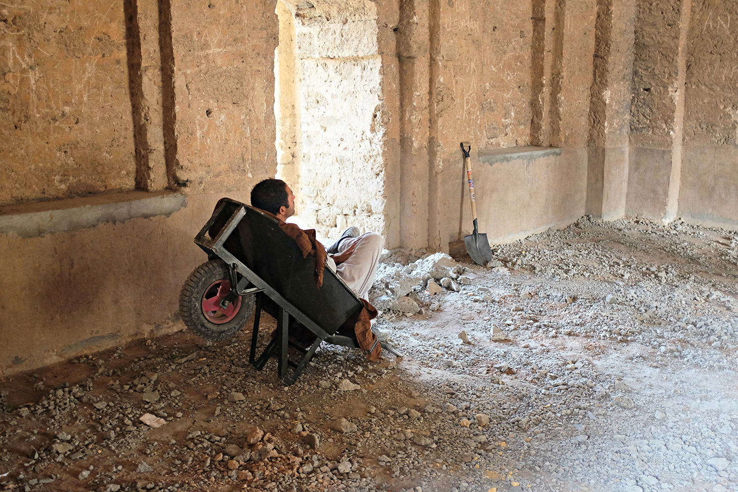 A labourer working on renovation at Rawat fort takes a break.