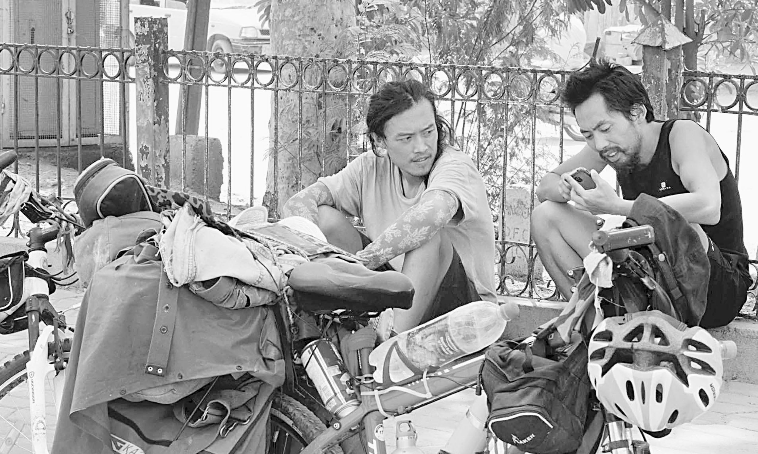 Two Chinese cyclists take a break on a footpath in Peshawar | White Star