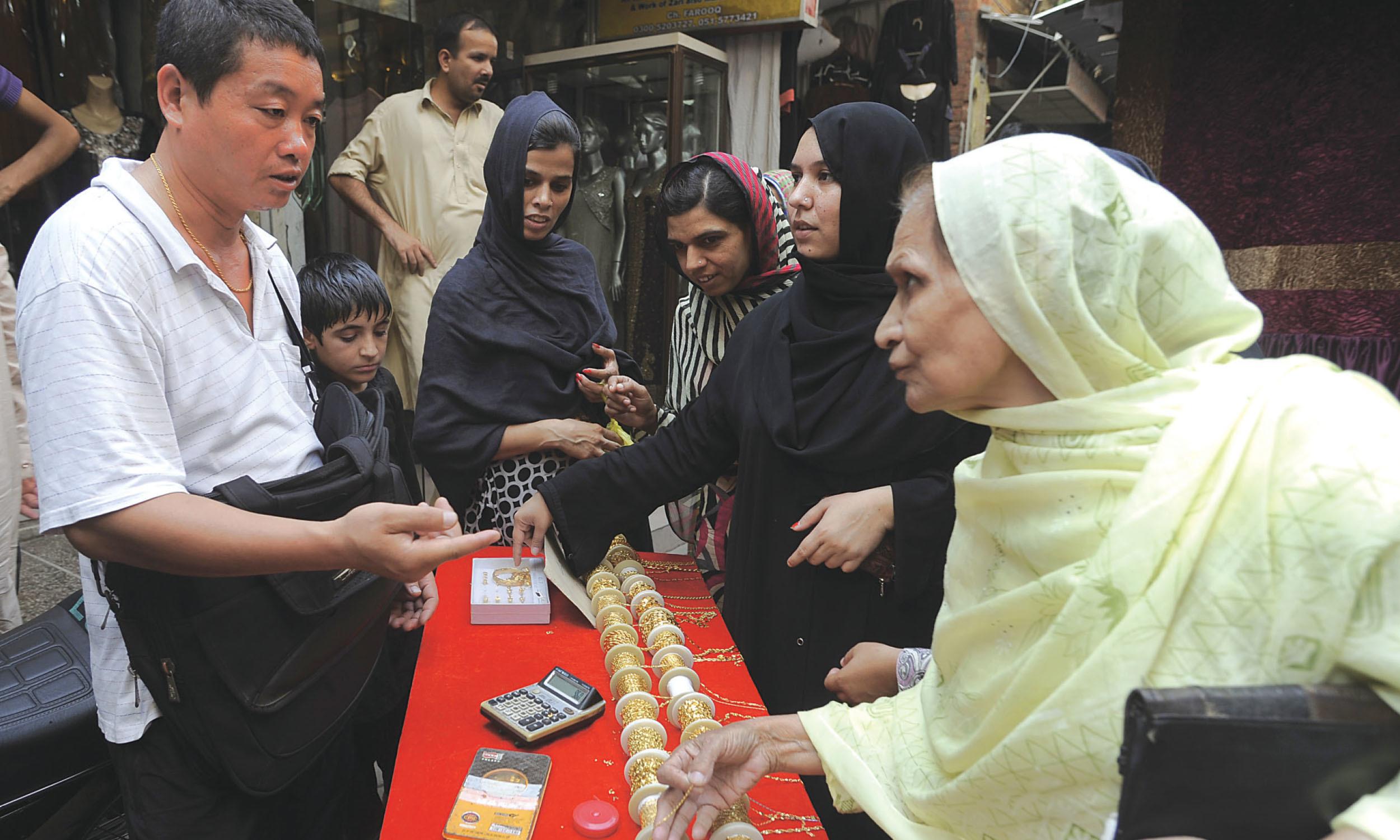 Women buy jewellery from a Chinese vendor in Rawalpindi's Raja Bazaar | Tanveer Shehzad, White Star