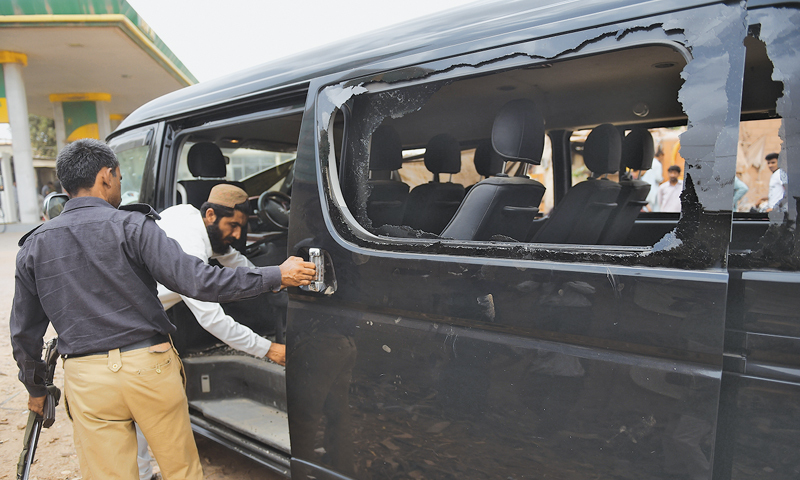 SECURITY personnel examine the vehicle after the attack.—AP