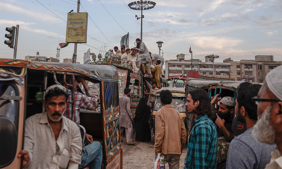 Commuters board overcrowded buses and autorickshaws along the route of Green Line in Karachi | Tahir Jamal, White Star