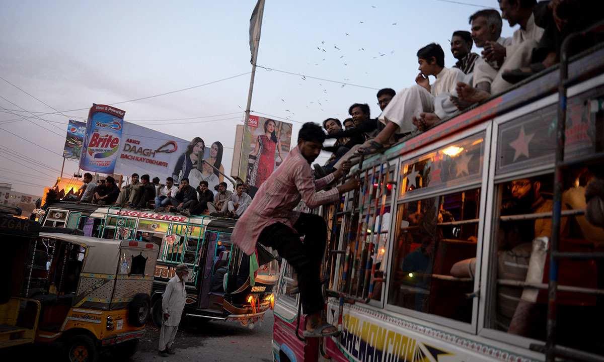 Passengers sit on top of crowded buses near the construction site of the Orange Line in Karachi | Tahir Jamal, White Star