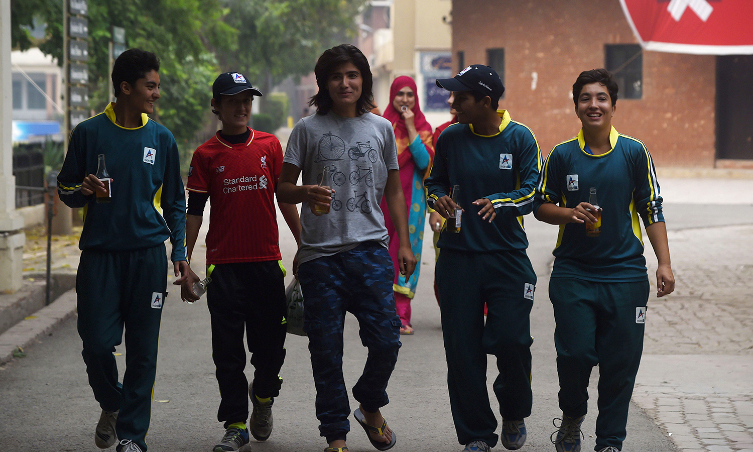 Diana Baig shares a light moment with her colleagues at a football club in Lahore. — AFP