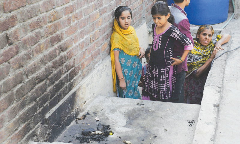 LAHORE: Family members stand at the site where a teenage girl was burnt alive by her mother on Wednesday.—AFP