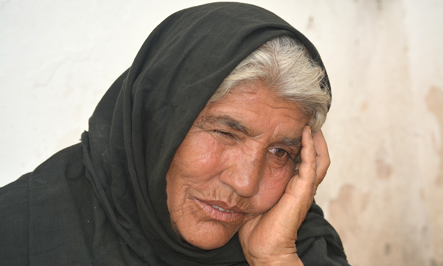A woman whose goods were confiscated waits outside the Hayatabad police station.