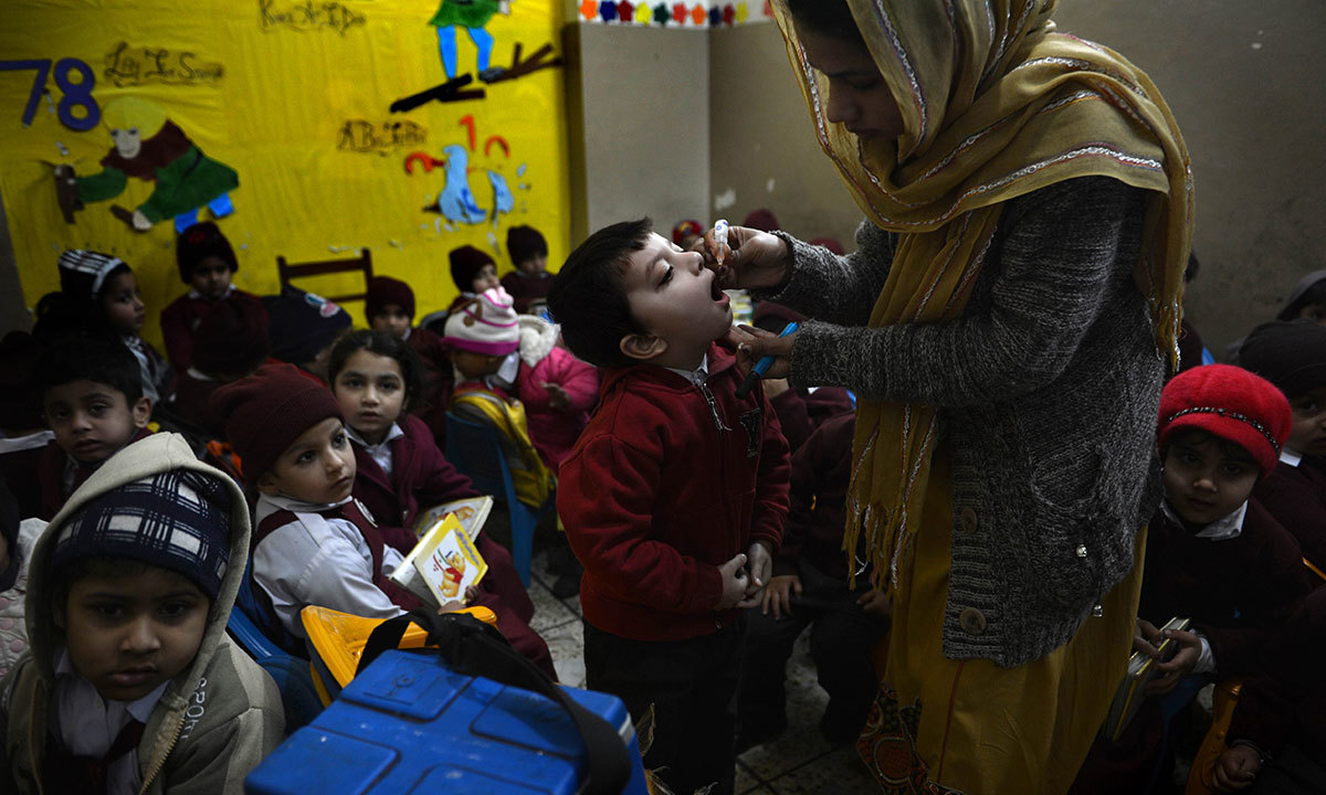 A child receives polio vaccination drops from a medical volunteer at a school in Rawalpindi on January 21, 2014 – AFP