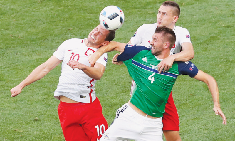 NICE: Poland's Grzegorz Krychowiak (L) and Artur Jedrzejczyk go for a header with Northern Ireland's Gareth McAuley during their Group 'C' match at the Allianz Riviera Stadium.—AP