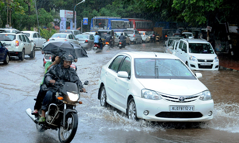 This file photograph taken Indian commuters as they make their way along a waterlogged road during heavy monsoon rains in Kochi.— AFP