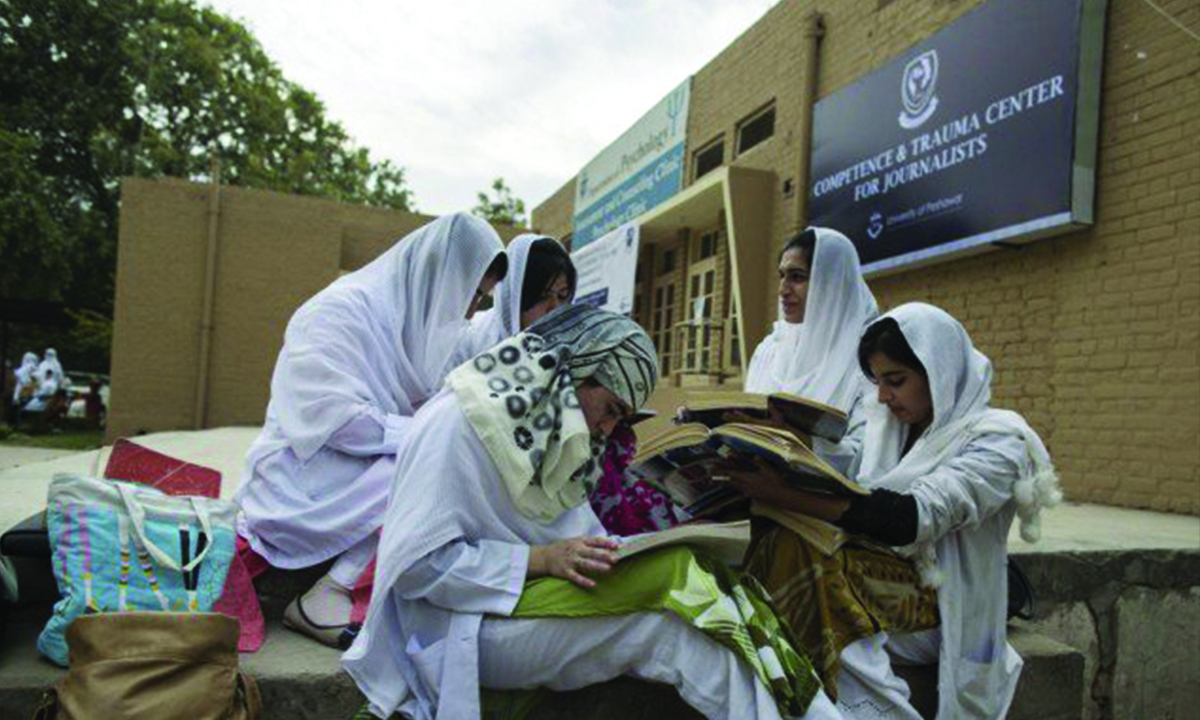Psychology students study outside the Competence and Trauma Centre for Journalists at the University of Peshawar | AFP