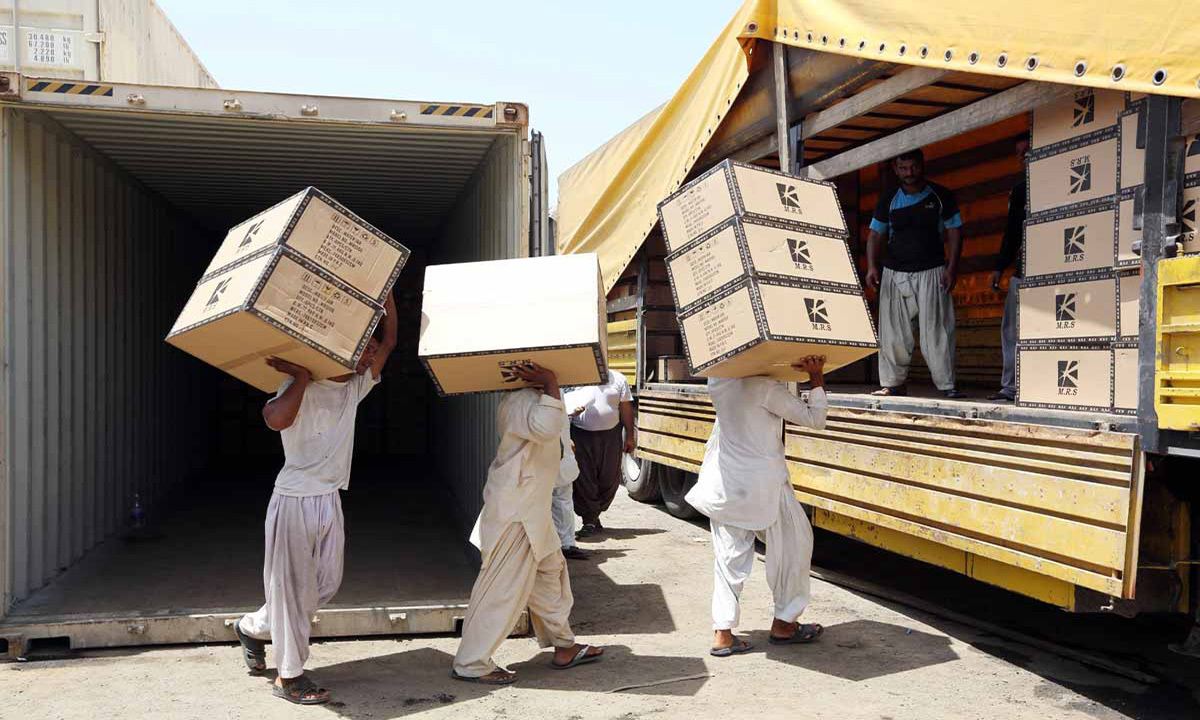 Workers transfering goods from a cargo container to trucks at the Kalantari port in city of Chabahar, Iran | AFP