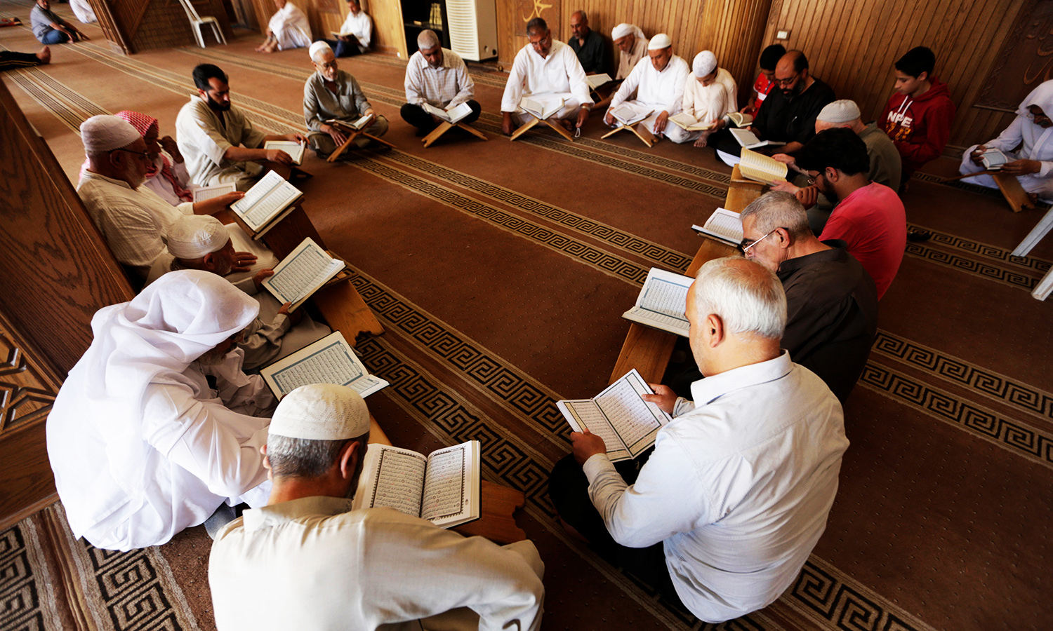 Men read the Holy Quran at the Grand Mosque during the holy month of Ramazan in the rebel-controlled area of Maaret al-Numan town in Idlib province, Syria, June 17, 2016. ─ Reuters