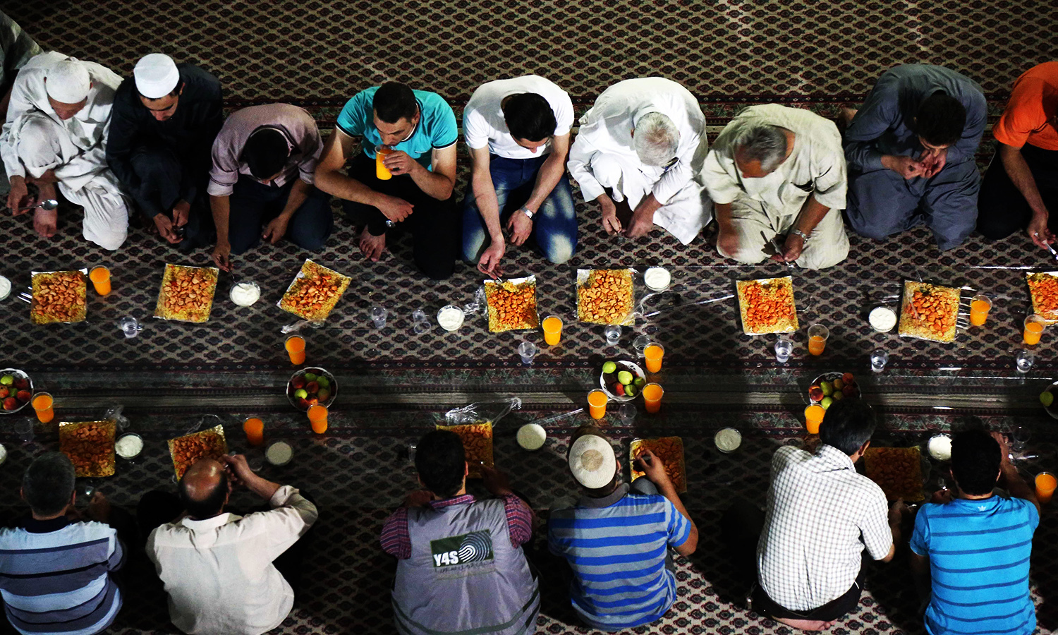 Syrian Muslim worshippers break the fast with an Iftar dinner distributed by a charity at a mosque on June 17, 2016 in the rebel-controlled town of Hamouria, in the eastern Ghouta region on the outskirts of the capital Damascus. ─ AFP